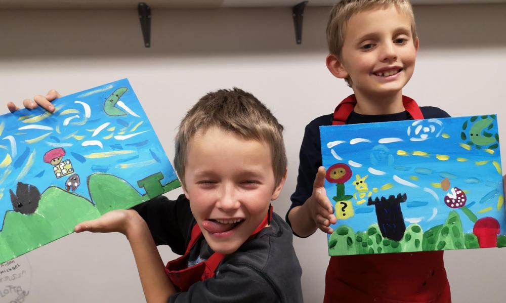 Two students showing off their Super Mario Painting